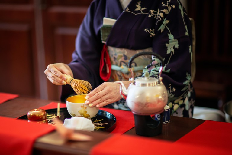 A woman wearing a kimono during a traditional Japanese tea ceremony