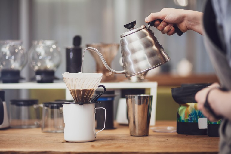 Barista pours over coffee in funnel. Barista's hand hold metal kettle with boiling water Immerse yourself like a local and learn about the city's thriving coffee scene