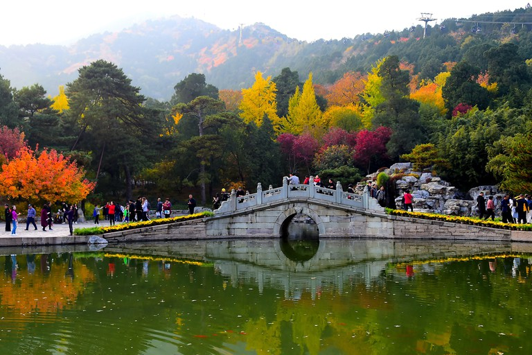 People walk on a bridge in Xiangshan Park in Beijing
