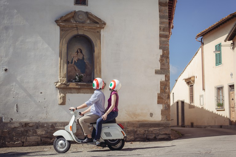 Couple looking at church painting from moped,
