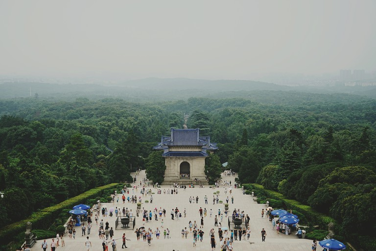 Crowd Visiting Sun Yat-Sen Mausoleum Surrounded By Trees Against Sky