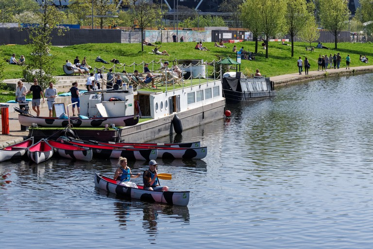 People enjoying sunny spring weather on the River Lea in Hackney, London England United Kingdom UK