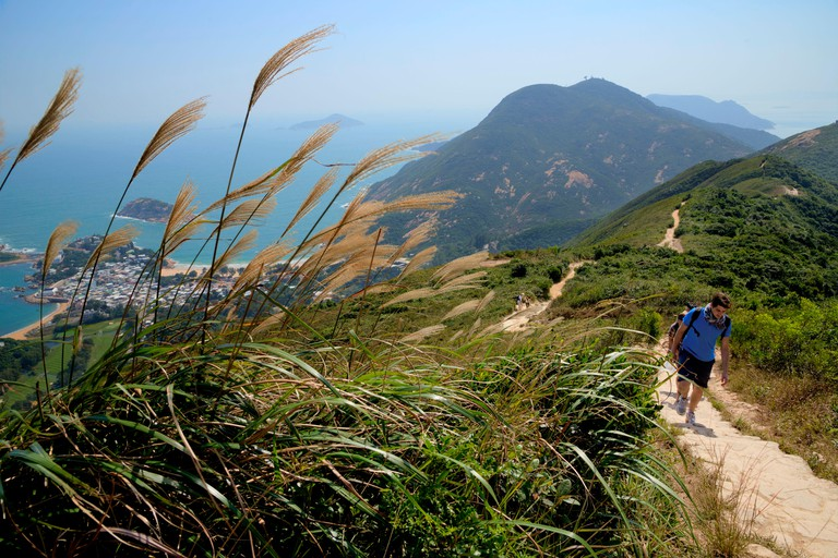 China Hong Kong Hong Kong Island Peninsula of Aguilar hiking trail of the Dragon's Back walkers on one smell with the village
