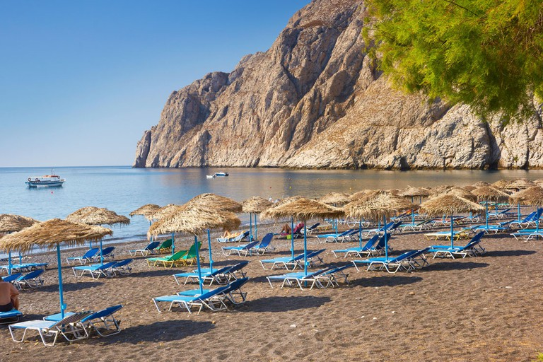Beach chairs and sun umbrellas at Kamari Beach (southeastern part of the Santorini), Santorini Island, Greece