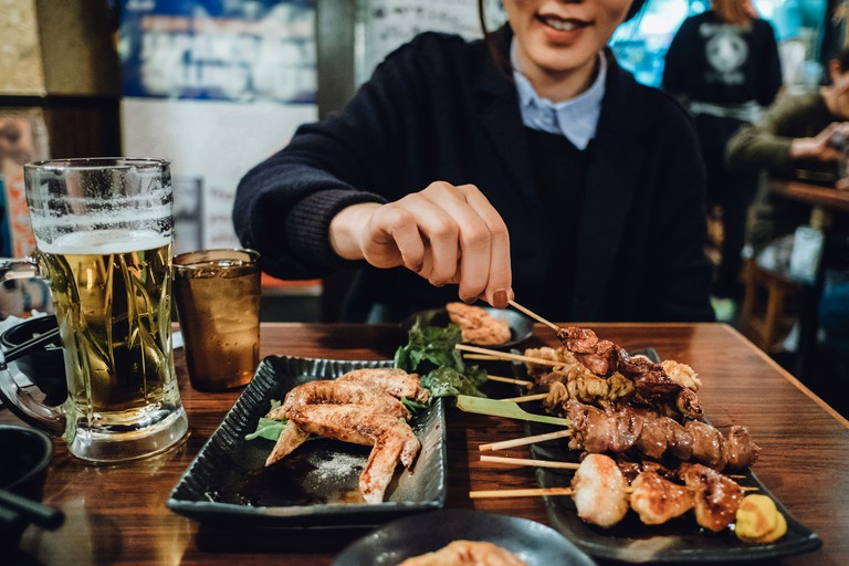 Cropped image of woman enjoying traditional Japanese yakitori and drinking beer in a Japanese style restaurant