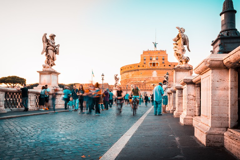 Ponte Sant'Angelo in front of Castel Sant'Angelo in Rome at sunset with tourists and statues