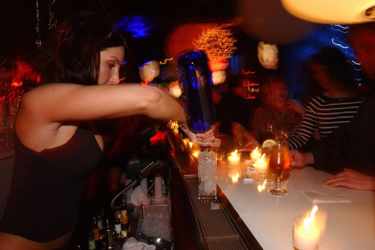 A bartender prepares a drink