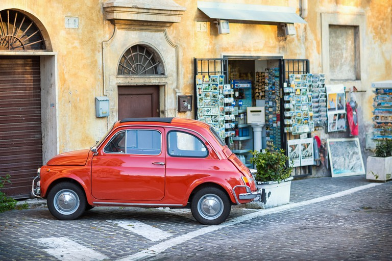 Red Fiat 500 parked in front of a souvenir shop.