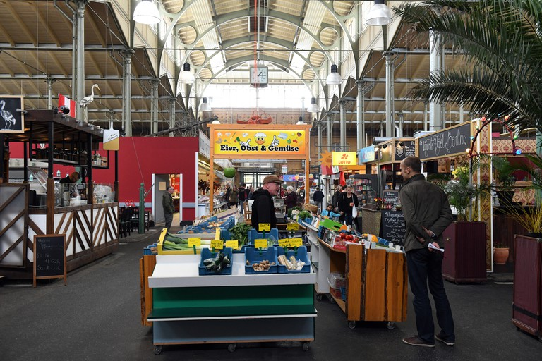 A trader selling vegetables in the Arminius-Markthalle market hall