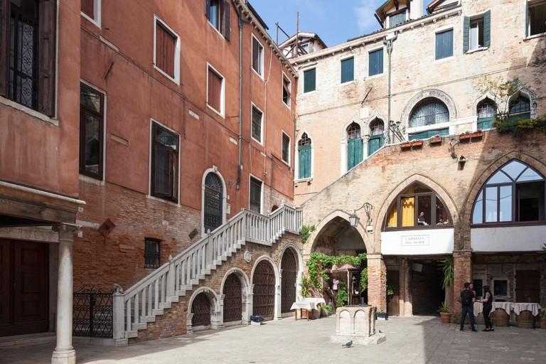 Campiello del Remer, Cannaregio, Venice, Veneto, Italy with its Gothic architecture. Taverna al Remer is a popular restaurant and bar with locals. Off