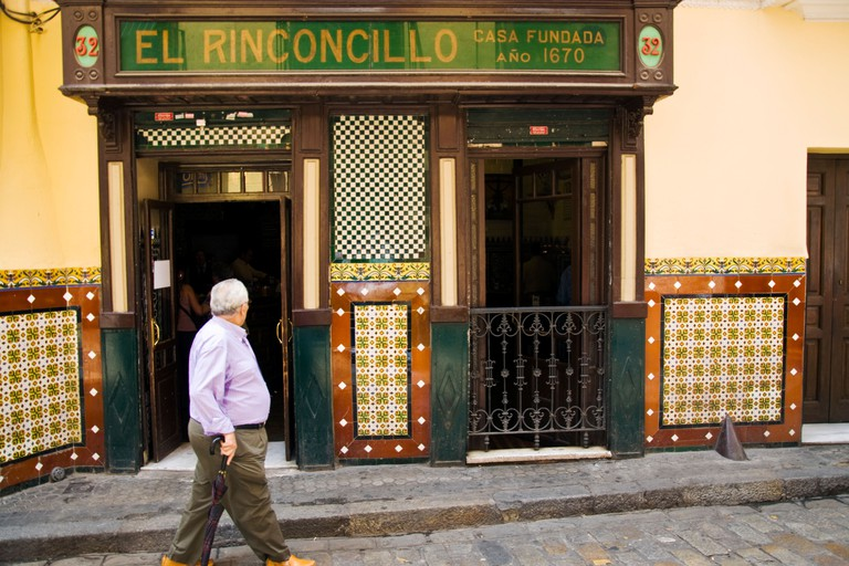 El Rinconcillo tapas wine bar cafe a man walking on street outside looking in