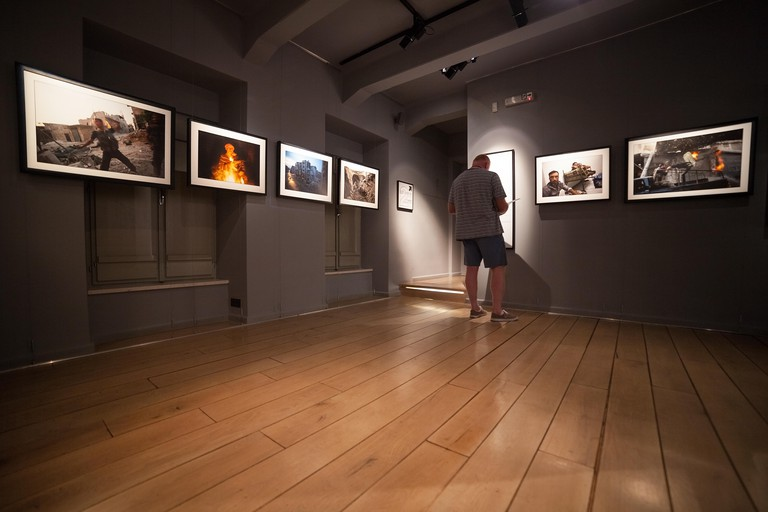DUBROVNIK, CROATIA - MAY 26, 2014: Tourist looking at photos in the War photo limited gallery. There is 350m2 of exhibition spac