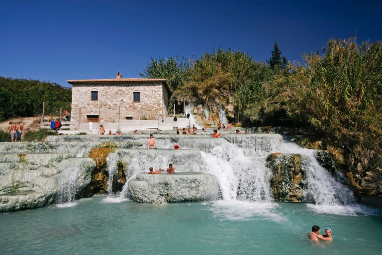 Group of people enjoying in a hot spring in Saturnia, Tuscany, Italy.