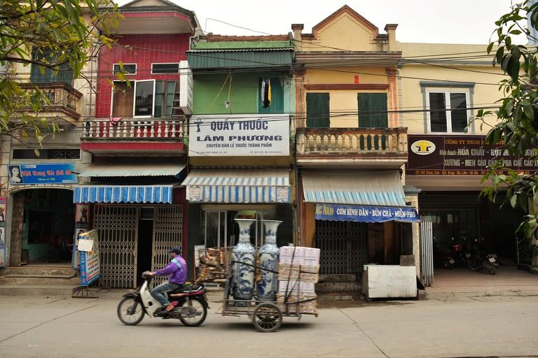 Motorcycle transporting large porcelain vases, pottery village of Bat Trang