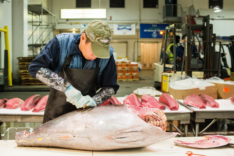 New York City, USA. Wholesale market stall employee cutting up a fresh tuna fish at the New Fulton Fish Market, Hunts Point, The Bronx.