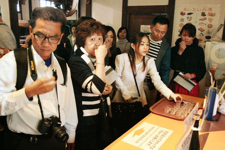 Tourists tasting Japanese sake at the Hakutsuru Sake Brewery Museum