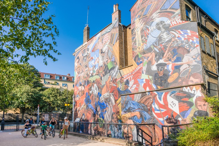A bicycle tour  people viewing the The Battle of Cable Street mural shadwell Cable street London England UK GB EU Europe
