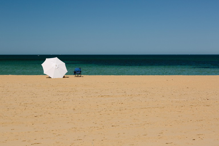 Mordialloc Beach in Melbourne. A large white umbrella near the waterline shelters its occupants.