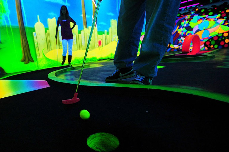 A couple play minigolf in a blacklight m