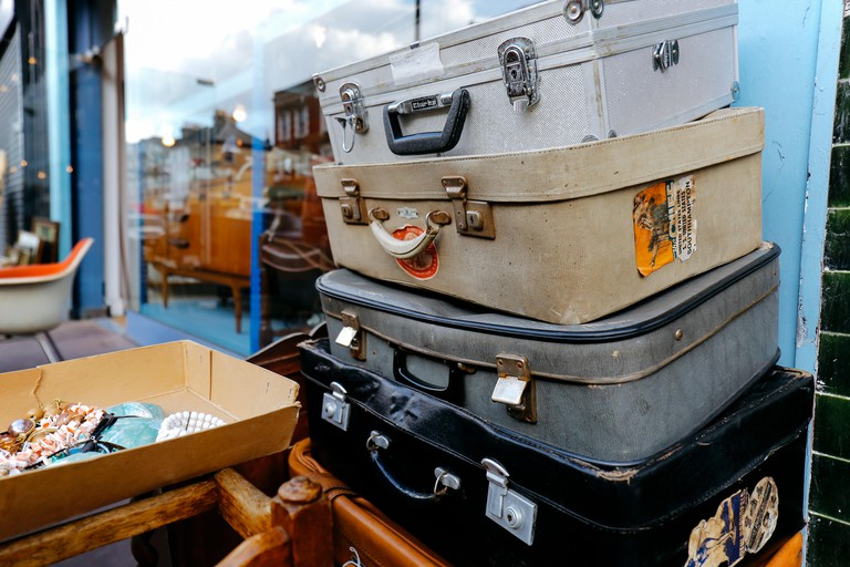 Stack of vintage suitcases with stickers on sale in Chatsworth Road Market. The market has a long heritage and is located on one of London's longest h