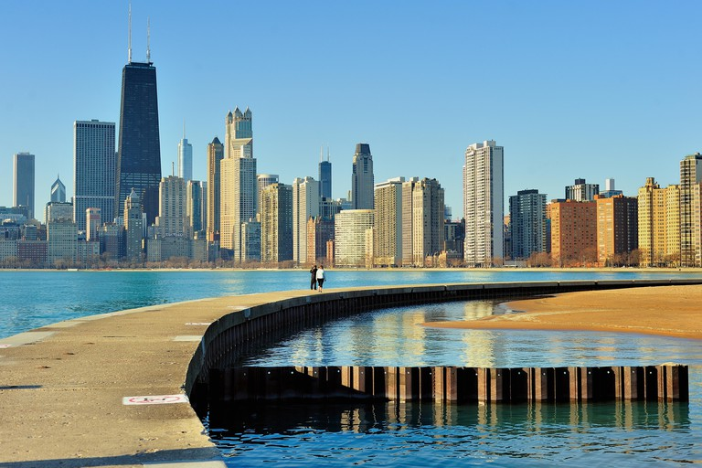 A couple walks along a breakwater that separates Lake Michigan from a small pool at Chicago's North Avenue Beach. Chicago, Illinois, USA.