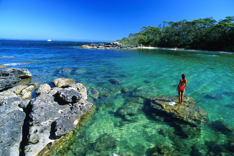 A woman standing on a rock at a bay under blue sky, Honeymoon Bay, Jervis Bay Marine Park, New South Wales, Australia