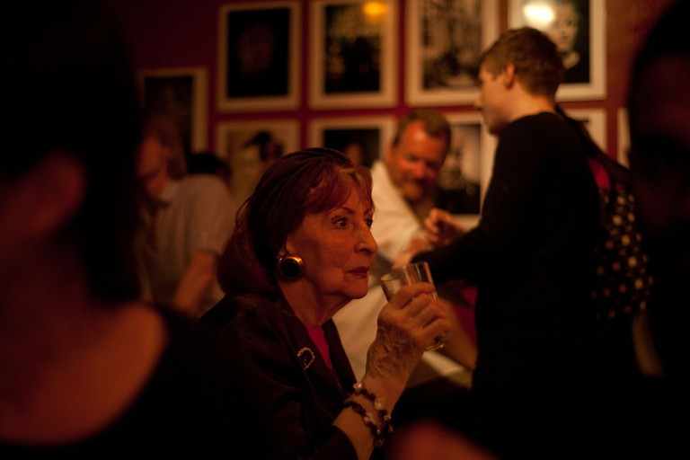 Manchester, UK - 4 August 2012: a senior woman sips her drink while listening to live music at the Matt & Phreds bar