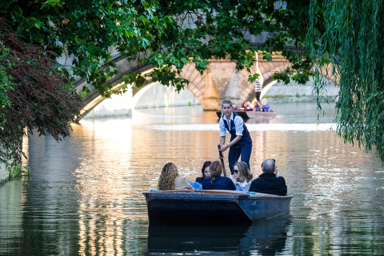 Cambridge Punting / Cambridge Tourism - Tourists get a guided punt tour on the River Cam through Cambridge University College grounds