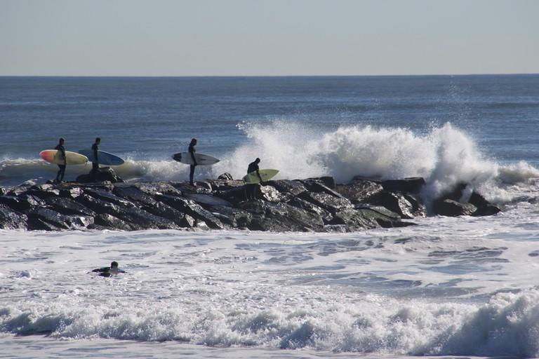 Surfers on a jetty with big waves, Rockaway beach, NYC