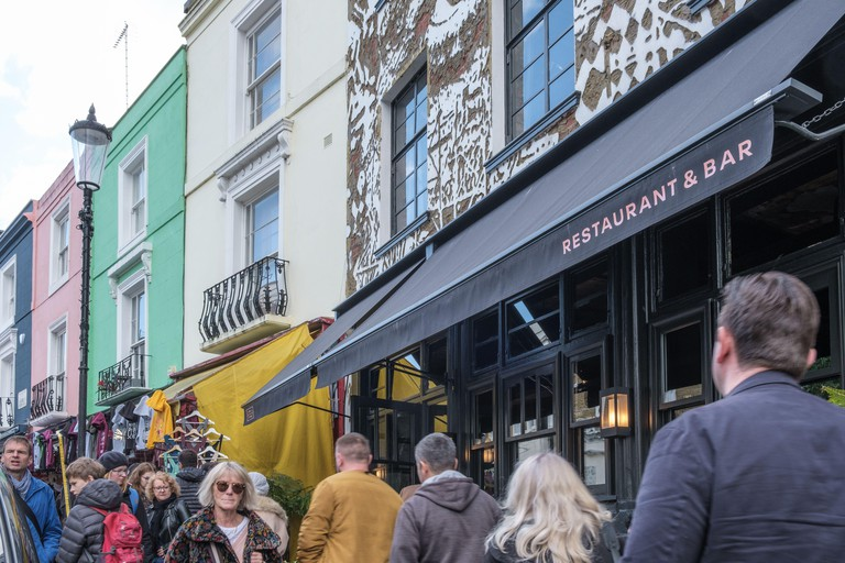 Gold restaurant & bar with mural of Eye Contact on facade of building, Notting Hill