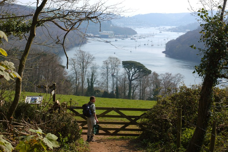 A walker enjoys the view of River Dart Valley in South Devon between Kingswear and Greenway