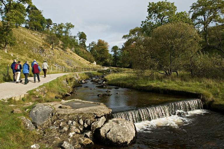 Group of adults walking alongside the beck on a nature walk towards Ingleborough Cave Yorkshire dales England UK