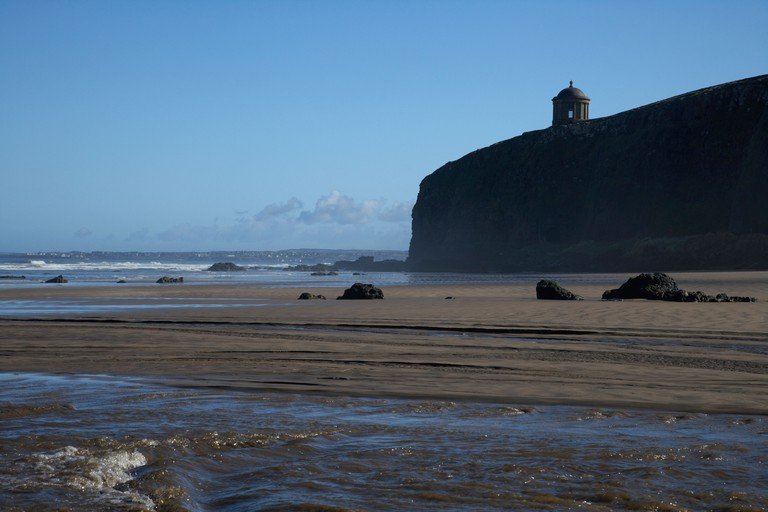 river running through Benone beach and Mussenden Temple on clifftop downhill county londonderry derry northern ireland