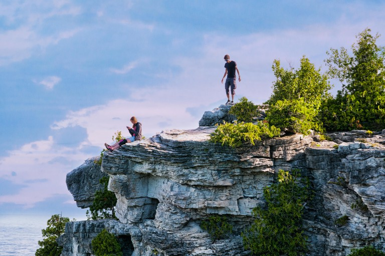 two teens standing on high cliff lookout at Bruce Peninsula National Park
