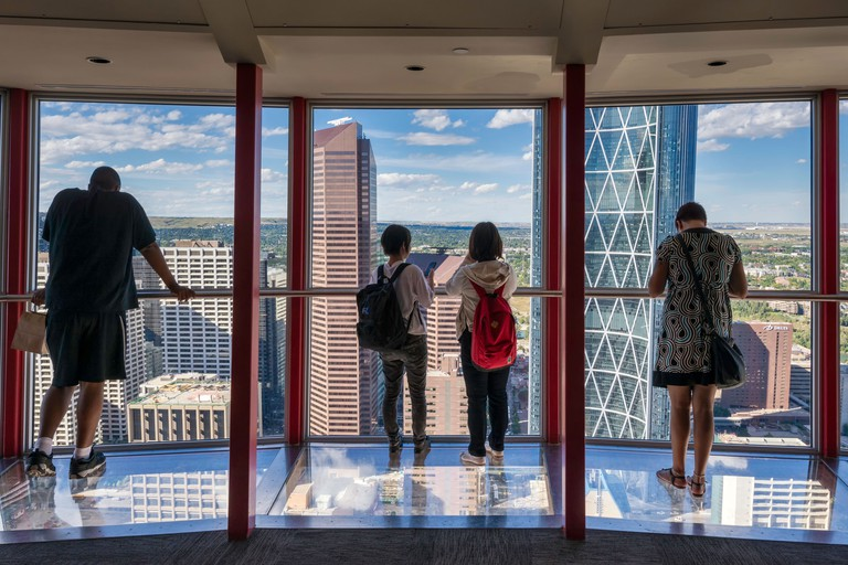 Visitors looking at downtown, standing on glass floor on top of Calgary Tower, Calgary, Alberta, Canada