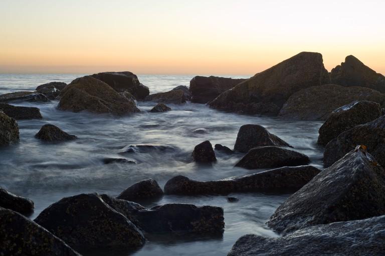 The sun sets over a rocky portion of Coronado Beach on Coronado Island