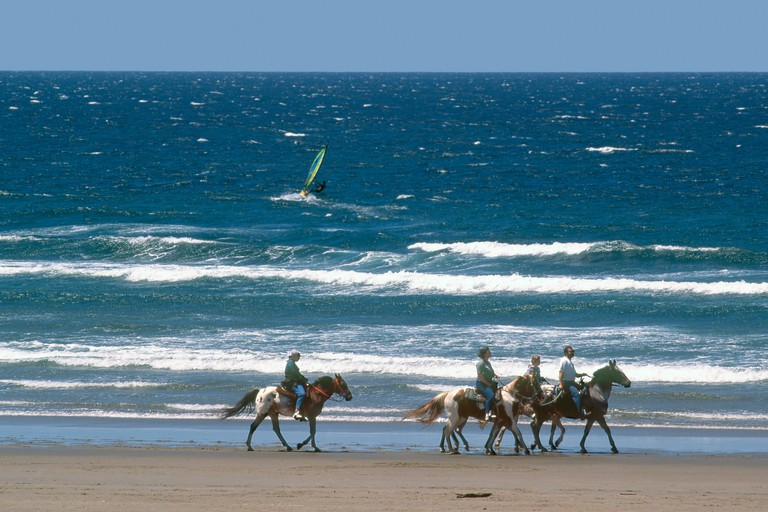 USA, Northern Oregon Coast, Manzanita, People horseback riding on beach