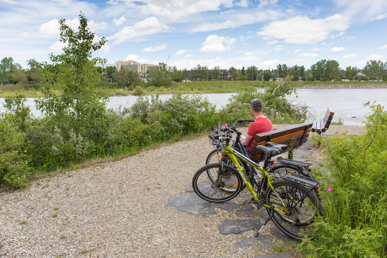 A man is sitting on Bench in Edworthy Park with two bikes beside him along Bow River in Calgary, Alberta, Canada