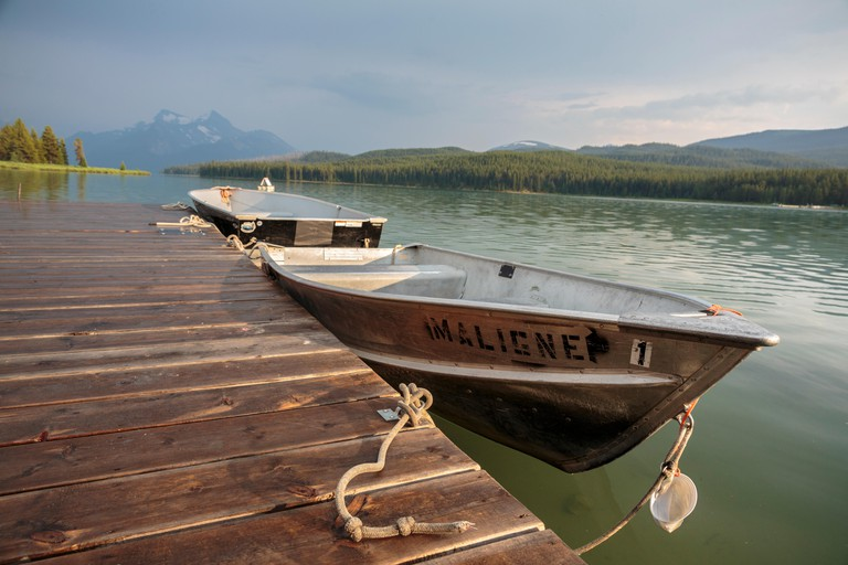 Evening light over Jasper National Park's Maligne Lake and boats available for rent at the historic Curly Phillips Boathouse.