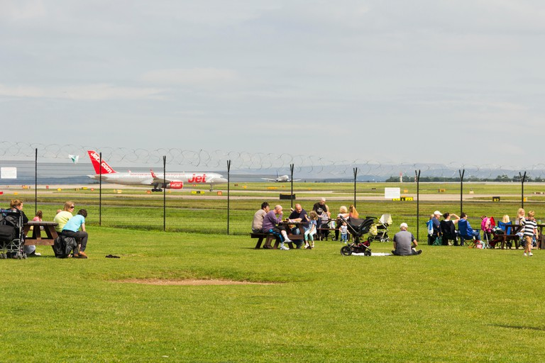 Families visiting Manchester airport's Runway Visitor park, watching the  aircraft come and go.