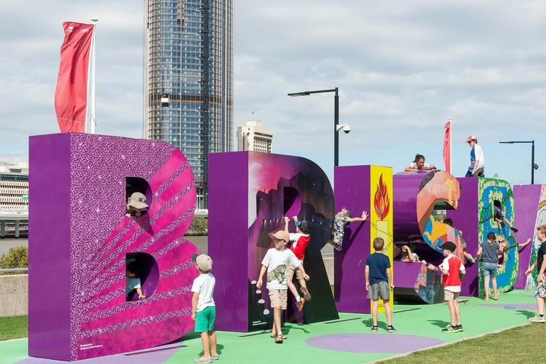 Children playing on Brisbane sign at South Bank Parklands