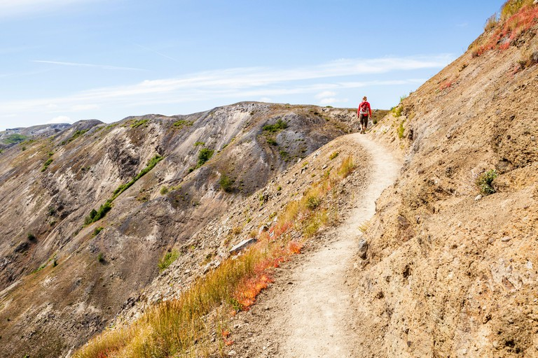 A woman walking along a trail cut into a steep hillside, Johnston Ridge Trail, Mount St Helens National Monument, Washington, USA.