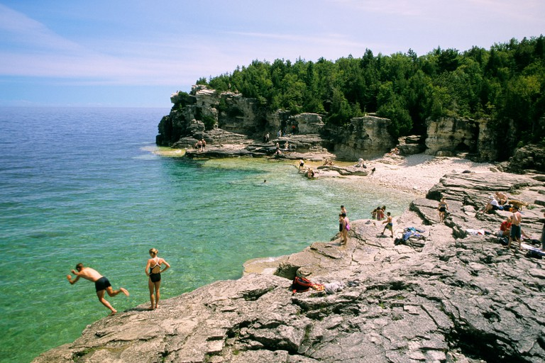 Swimmers enjoy the cool blue waters of Georgian Bay at Indian Head Cove, Bruce Peninsula National Park, Ontario, Canada.