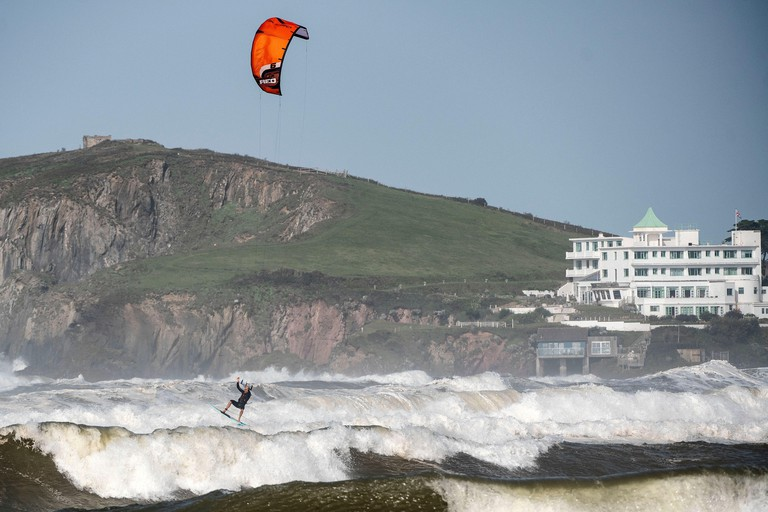 A kite surfer makes the most of the conditions at Bantham beach in South Devon as Storm Ellen brings strong winds across the United Kingdom.