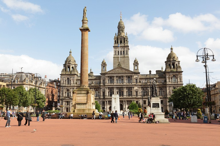 Looking East across George Square with the old red tarmac to the City Chambers in Glasgow City Centre, Scotland, UK