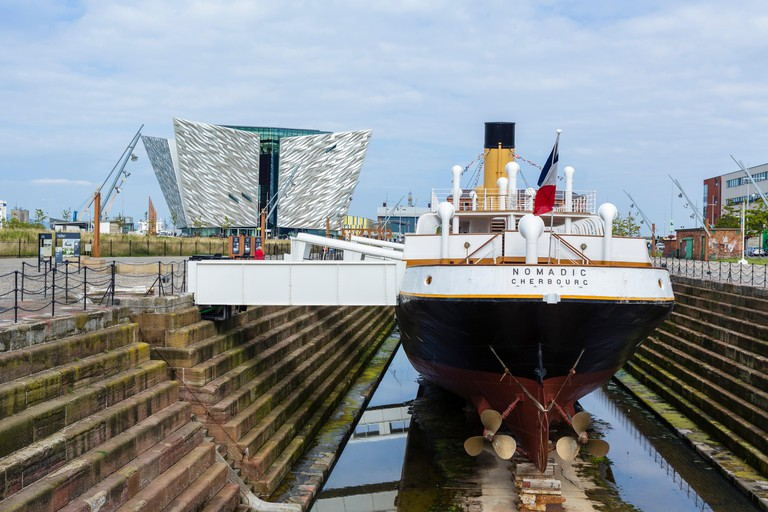 The steamship tender SS Nomadic with Titanic Belfast museum behind, Titanic Quarter, Belfast, Northern Ireland, UK