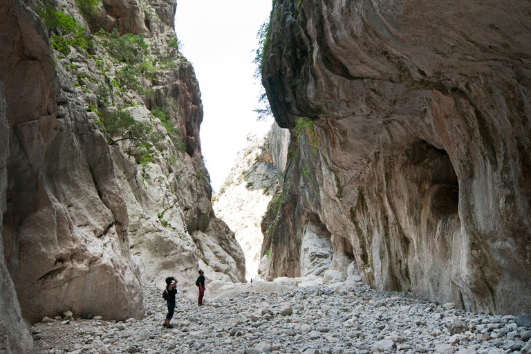 People hike inside Gorropu gorge, one of the highest canyon in Europe, Supramonte zone of Urzulei and Orgosolo, Sardinia, Italy. Image shot 05/2014. Exact date unknown.