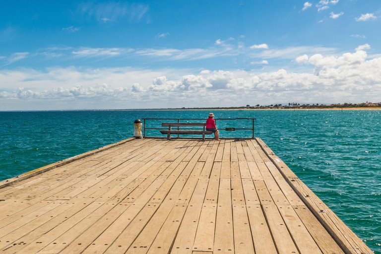 View to the end of the Frankston Pier, Melbourne, Australia. A woman sits on a bench watched the time come in