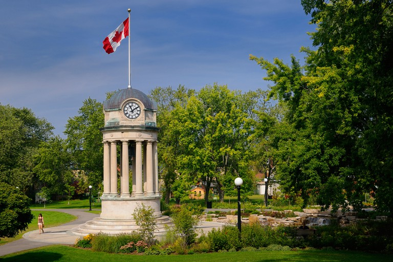 Old City Hall Clock Tower and fountain in Victoria Park Kitchener with Canadian flag