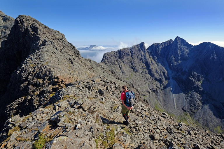 A climber approaching the summit of Sgurr Dearg on the Cuillin Ridge of Skye with Sgurr Alasdair in the background